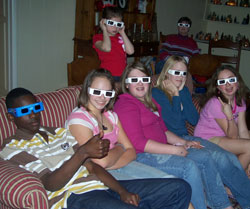 Several youth sitting down and wearing 3D movie glasses